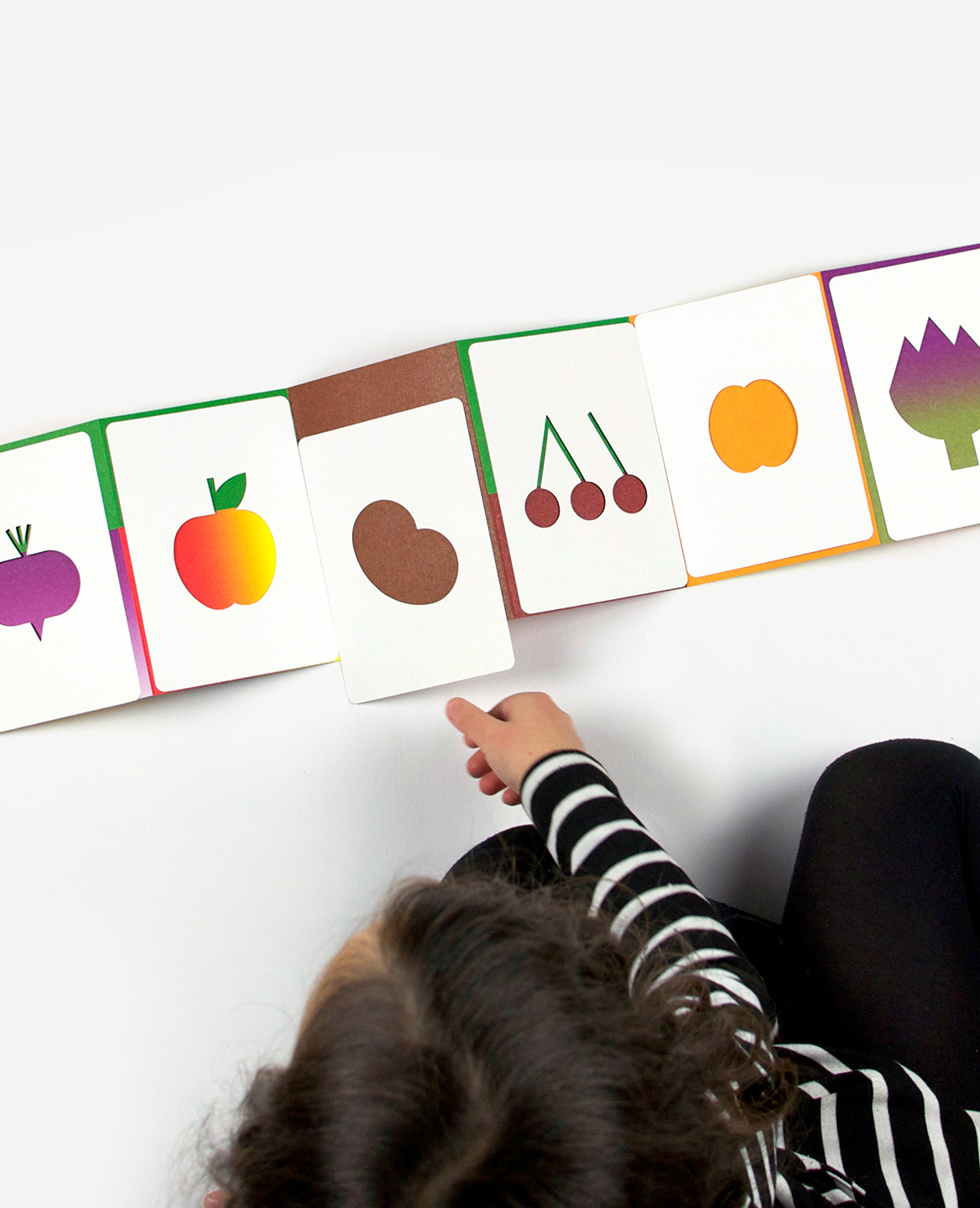 Child playing with the book-game Hello tomato