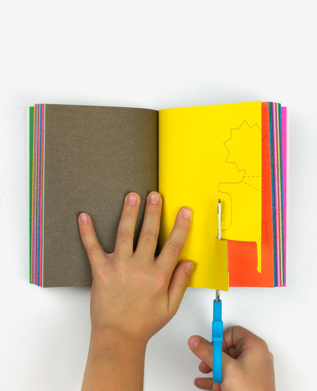 Mains d'un enfant découpant un lion dans le livre Zoo in my hand de Inkyeong & Sunkyung Kim publié par les Éditions du livre
