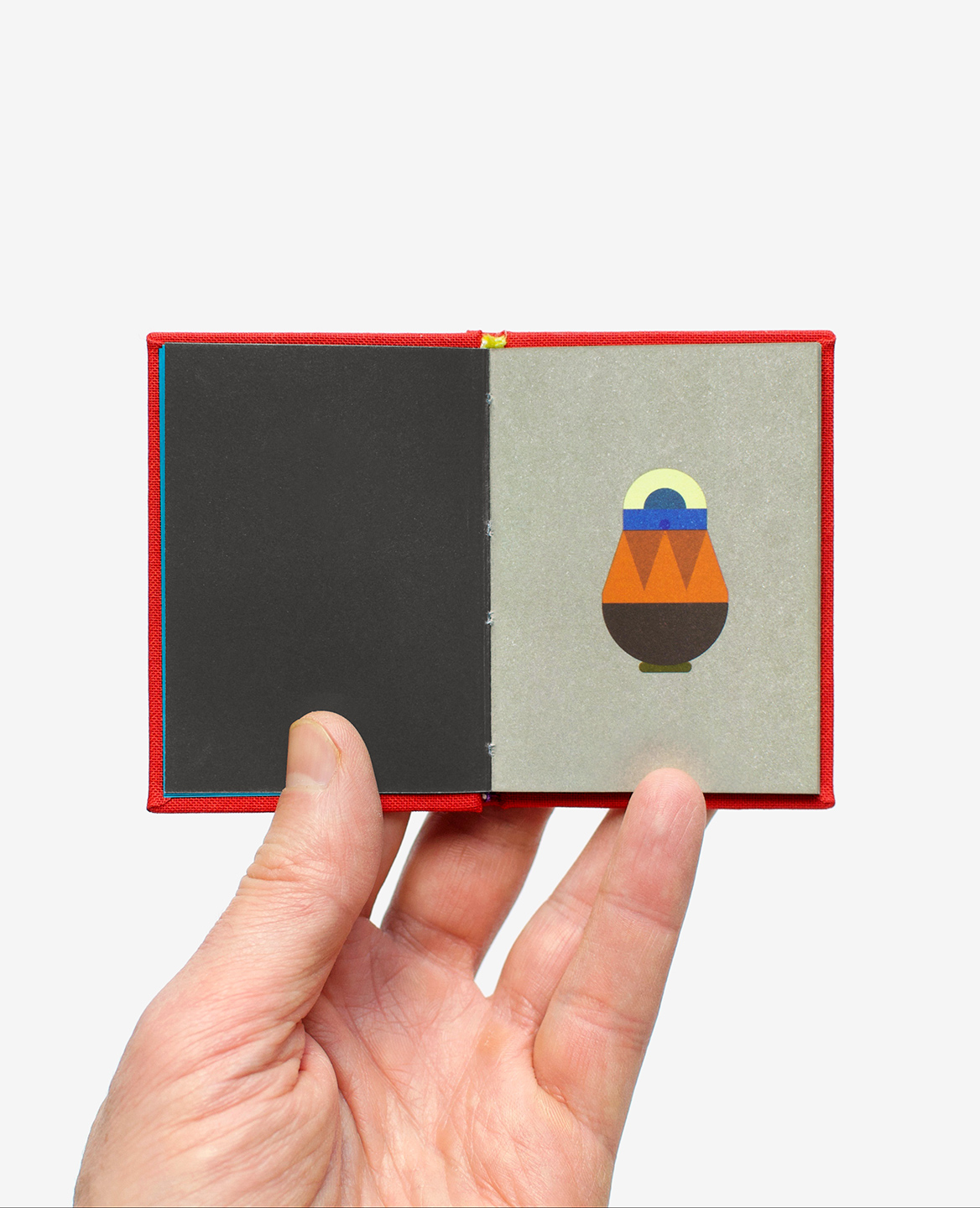 Hand holding the miniature book Matryoshka by Fanette Mellier published by Éditions du livre